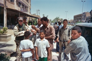 medic giving medical care to iraqis in al kindi district, outside cafe